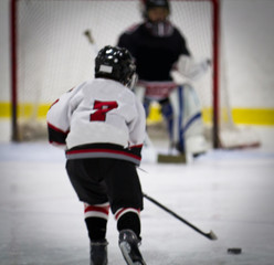 Child playing ice hockey on a breakaway