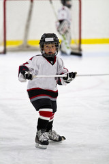 Child playing minor hockey in the arena