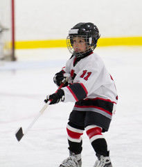 Child making a pass while playing ice hockey
