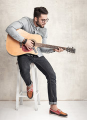 handsome man playing an acoustic guitar against wall