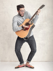 handsome funny man playing an acoustic guitar