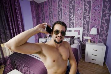 Hombre resacoso en el dormitorio llamando por telefono
