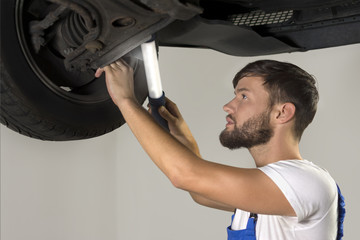 Male car mechanic working under car