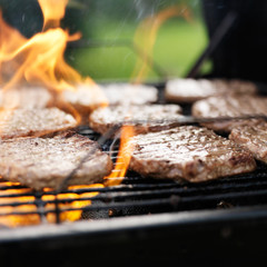 grilling hamburgers on charcoal grill with flames