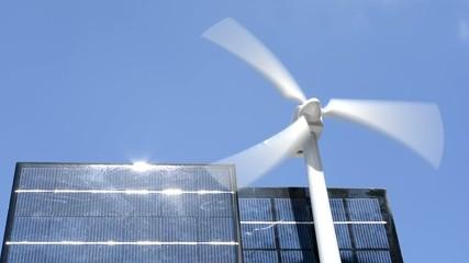 青空の下のソーラーパネルと風力発電の模型