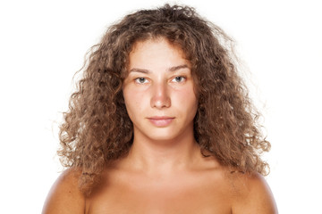 serious young woman without make-up and curly hair