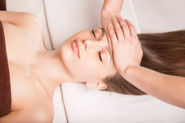 Young bright woman receiving head massage