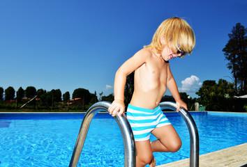 Bambino sulla scaletta della piscina