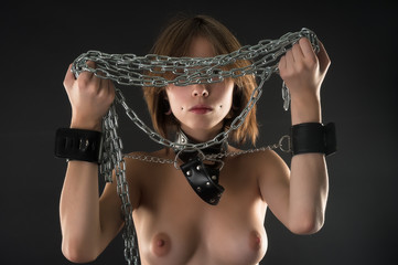 Pretty sexy woman with belts, collar and chains