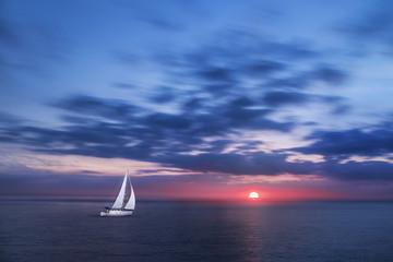 Voilier en Pleine Mer durant un Coucher de Soleil