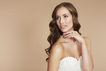 Young bride in wedding dress looking away, studio shot .