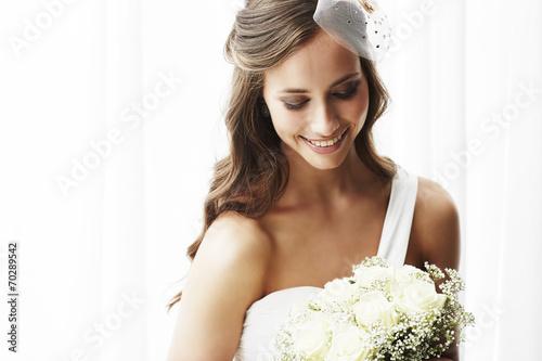 Young bride in wedding dress holding bouquet, studio shot . - 70289542