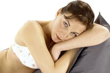 Frau in Unterwäsche liegt auf Sitzkissen