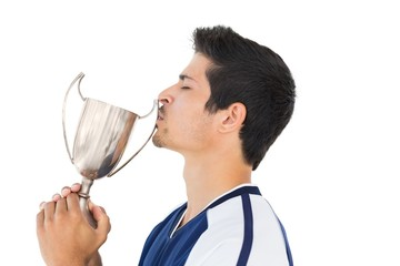 Football player kissing winners cup