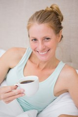 Happy blonde drinking coffee in bed