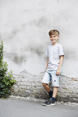 Portrait of young leaning against wall, smiling.