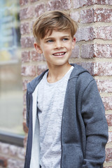 Young boy leaning against wall, looking away.