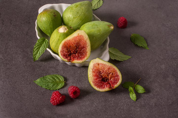 A close-up of assorted fresh figs and raspberry