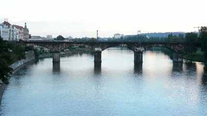 bridge for train over the river - city with buildings - nature