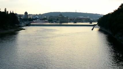Prague, river Vltava with city - sunset - sun reflection