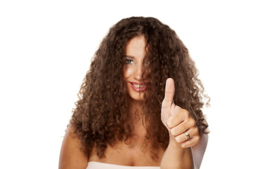smiling young woman with curly hair showing thumbs up