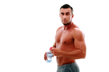 Handsome muscular man standing with bottle of water