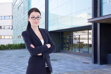 business woman standing on street against office building