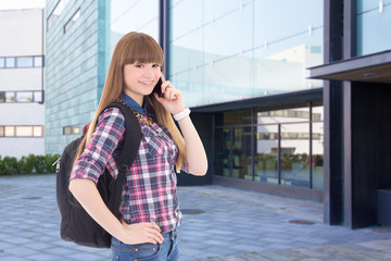teenage girl with cell phone standing on street against school b
