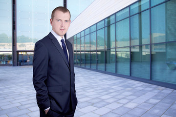 handsome business man standing on street against office building