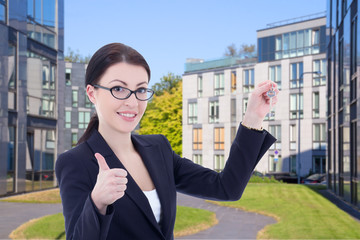 real estate agent with key standing on street against modern bui