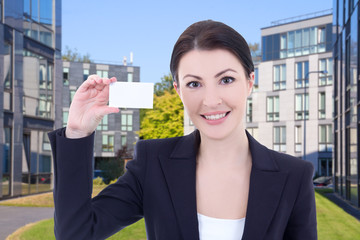 beautiful business woman showing visiting card on street against