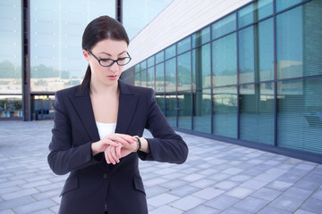 business woman checks time on her wrist watch standing on street