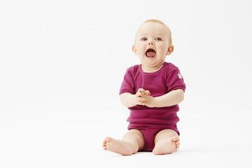 Baby girl sitting against white background.