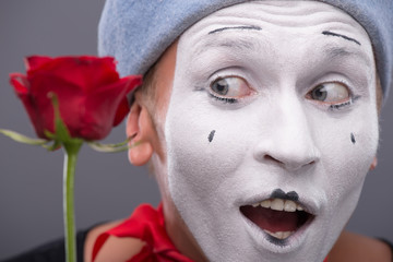 Waist-up portrait of young male mime holding a flower isolated o