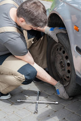 Mechanic changing wheel in car