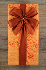 beautifully decorated gift box with bow on wooden
