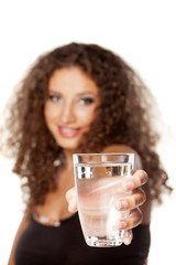 smiling young woman with curly hair offers a glass of water