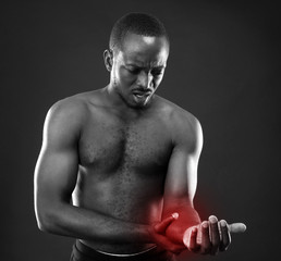 African man checking pulse over black background