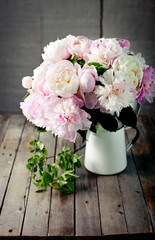 Bunch of peony flowers  in an enamel jar
