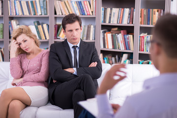 Unhappy couple talking to the psychologist and sitting couch