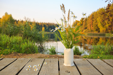 Bright autumn field bouquet in the vase at bridge on the pond