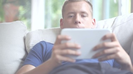Young man spending free time with tablet and relaxing movie