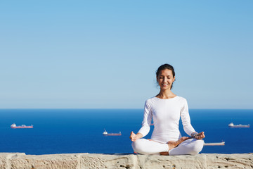 Woman seated in yoga pose on amazing sea background