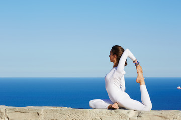 Beautiful woman in white clothes seated in yoga pose outdoors