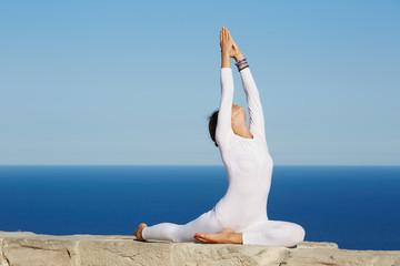 Pretty brunette woman makes yoga meditation at sunny evening