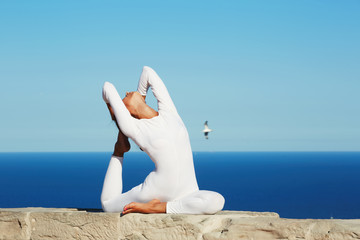 Brunette girl with beautiful body engage yoga at high altitude
