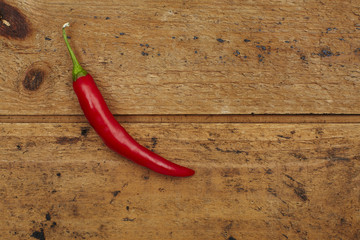 Red chili pepper against wooden background.