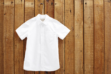 White short sleeved shirt hanging against wooden wall.