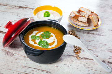Pumpkin soup with cream in ceramic pot