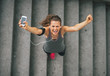 Leinwanddruck Bild - Portrait of happy fitness young woman with cell phone